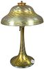 Tiffany Studios Favrile Glass Table Lamp having stepped dome shade with Favrile wave pattern in yellow, green, blue, and gold iridescence, resting on