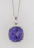 Platinum Pendant, with a 21.23 carat cushion cut tanzanite atop a conforming border of small round diamonds, with a pierced marquise shaped diamond mo