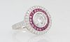 Lady's 18K White Gold Dinner Ring, with a central 1.53 carat round diamond atop a border of trapezoidal rubies, within a border of small round diamond